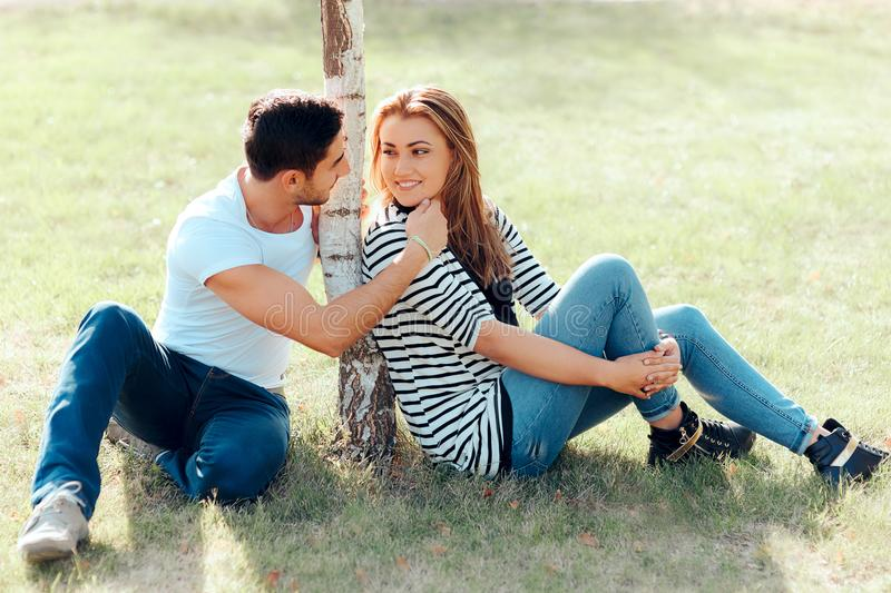 Young Man in Love Flirting with a Beautiful Girl in Outdoor Date. Romantic guy making affectionate gesture towards his new crush royalty free stock image