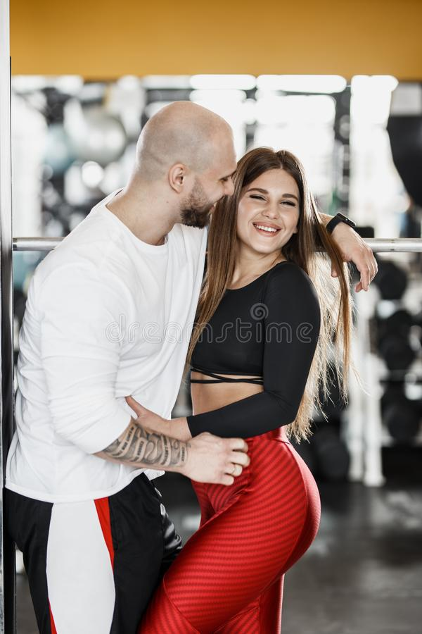 Romantic happy athletic couple. Strong man and slender beautiful girl are hugging in the modern gym next to the sport stock photo