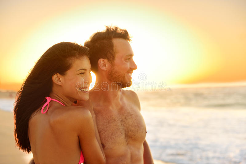 Romantic happy couple lovers on beach honeymoon. Having playful fun together during summer beach holidays. Cheerful young multiracial couple, Asian women and royalty free stock photo