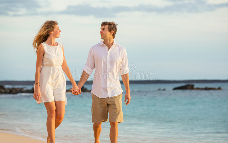 Romantic happy couple walking on beach at sunset. Smiling holding hands. Man and women in love royalty free stock photo