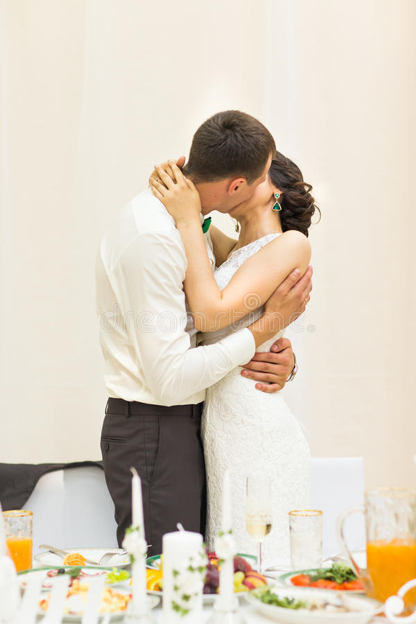 Romantic happy handsome groom kissing beautiful white dress bride at wedding reception royalty free stock images