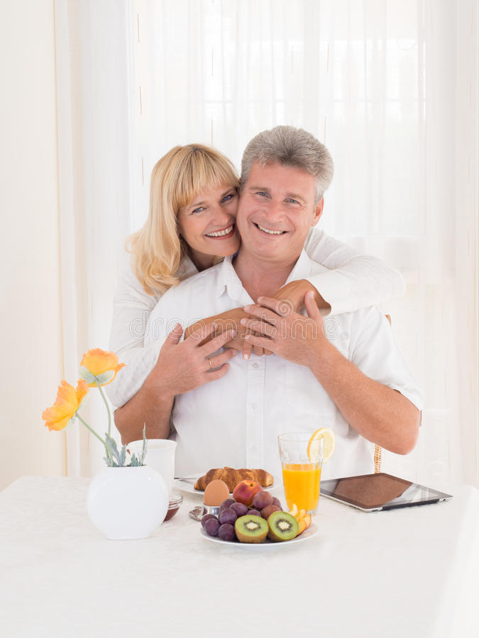 Romantic happy mature couple with beautiful smiles hugging on breakfast stock photography
