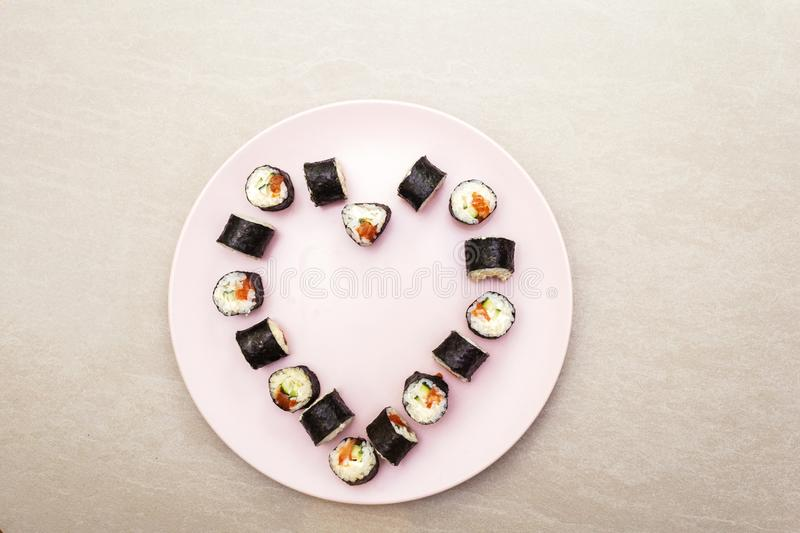 Romantic heart sushi dinner. Rolls with salmon, Philadelphia cheese and cucumber. Concept for Valentine`s Day or March 8th. On. Rosy plate, stone background royalty free stock images