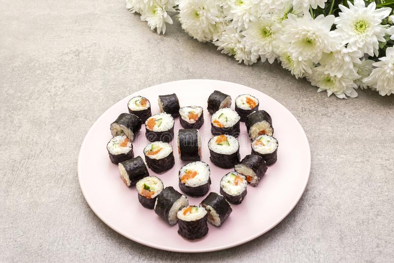 Romantic heart sushi dinner. Rolls with salmon, Philadelphia cheese and cucumber. Concept for Valentine`s Day or March 8th. On. Rosy plate with flowers, stone royalty free stock photo