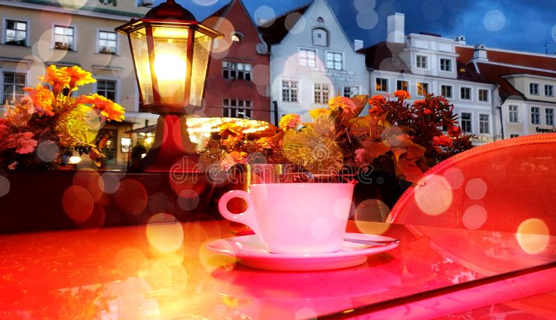 Romantic holiday city light Street cafe  bokeh blurring city light evening restaurant table cup of coffee on top view candle lamp. Romantic holiday  city light stock images