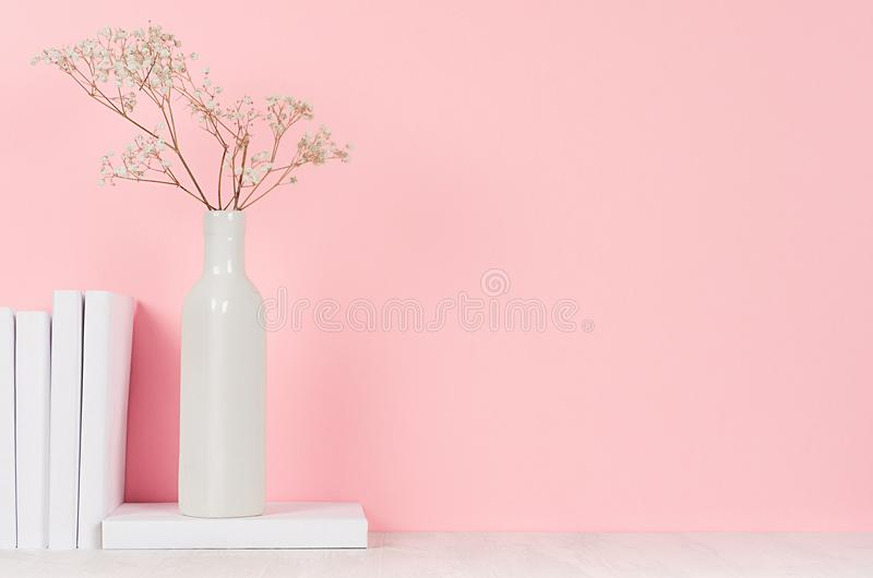 Romantic home decor of white dry flowers in vase and pile white books on light pink background. Romantic home decor of white dry flowers in vase and pile white royalty free stock images