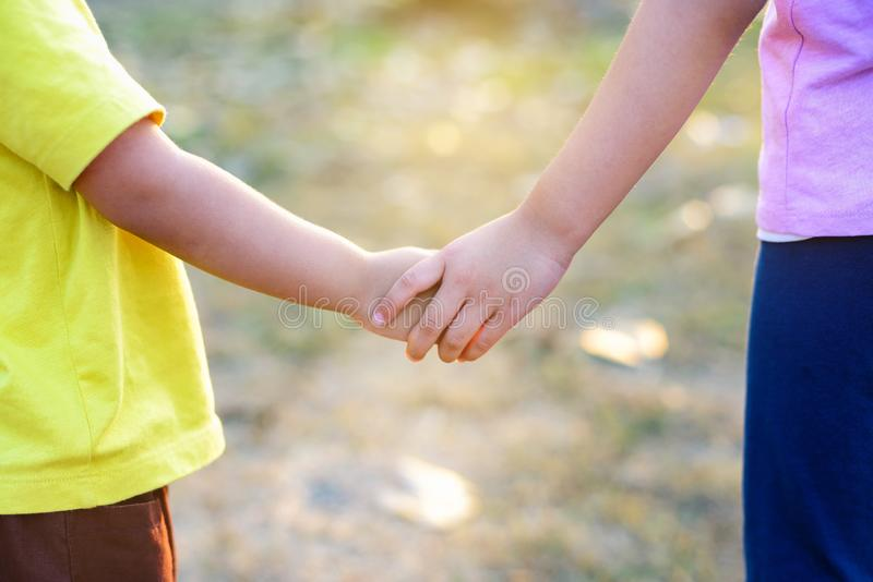 Older sister`s hand holding her brother`s hand together royalty free stock photo
