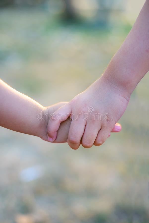 Older sister`s hand holding her brother`s hand together to take care. royalty free stock photo