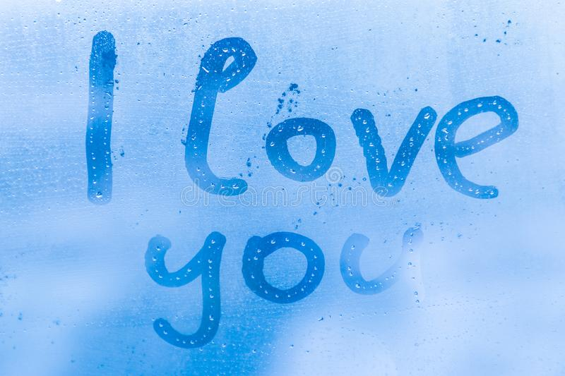The romantic inscription I love you on the blue evening or morning window glass royalty free stock image