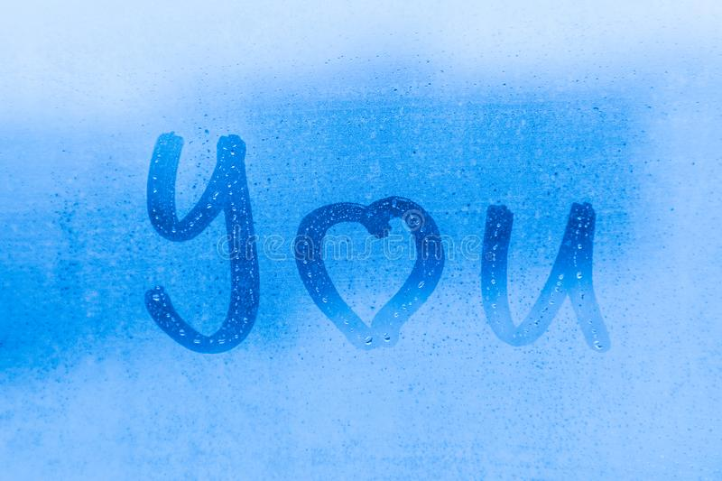 The romantic inscription I love you on the blue evening or morning window glass royalty free stock photography