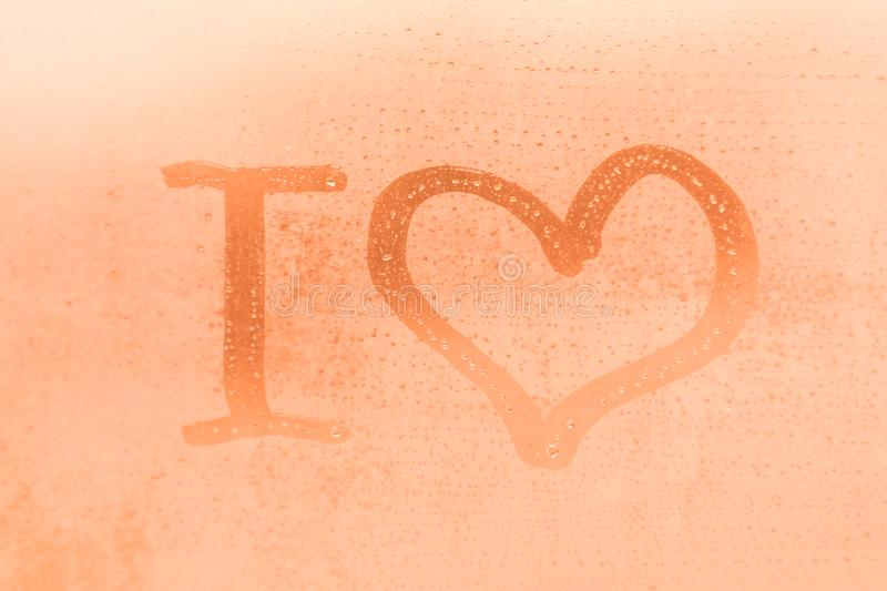 The romantic inscription I love you on the orange or pink evening or morning window glass royalty free stock photo