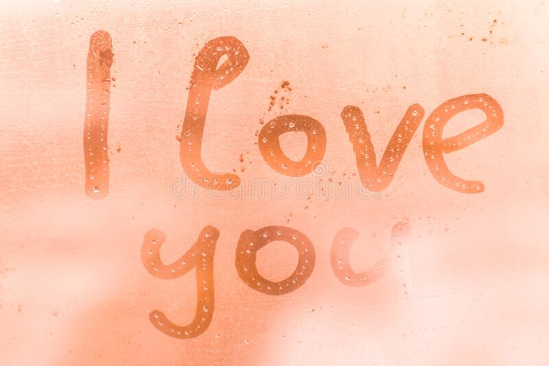 The romantic inscription I love you on the orange or pink evening or morning window glass royalty free stock images