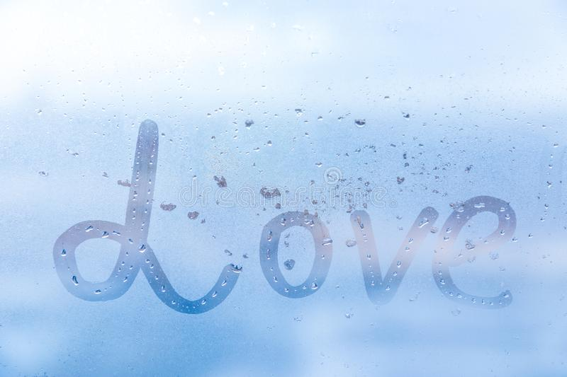 The romantic inscription love on the blue evening or morning window glass royalty free stock photography