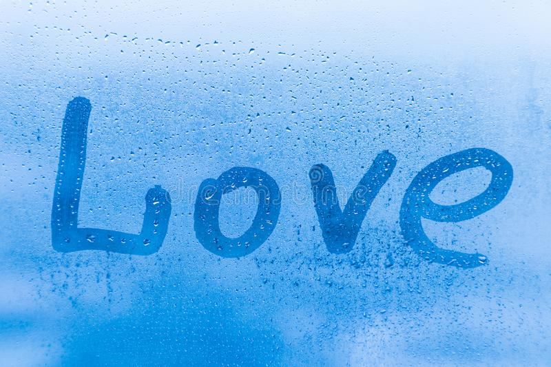 The romantic inscription love on the blue evening or morning window glass stock photo