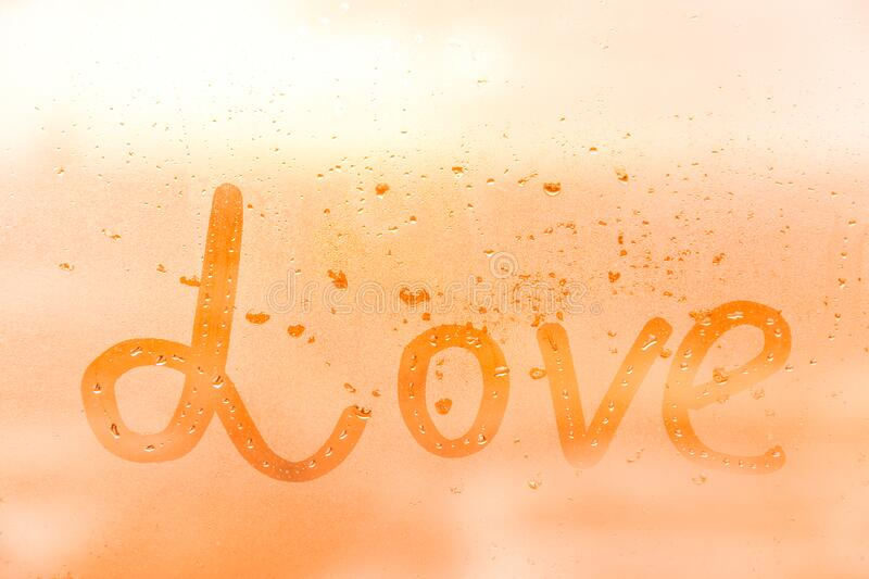 The romantic inscription love on the orange or pink evening or morning window glass. With drops stock images