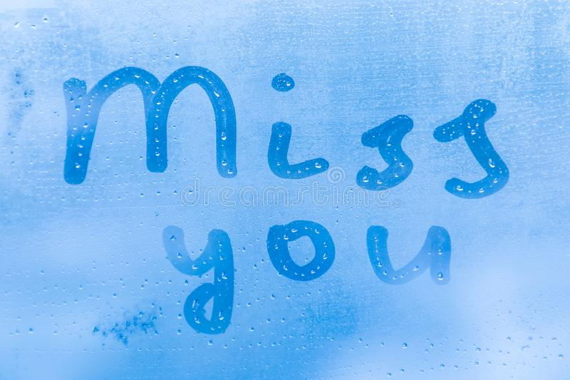 The romantic inscription miss you on the blue evening or morning window glass royalty free stock photography