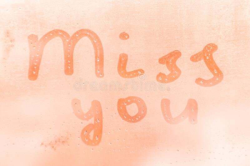 The romantic inscription miss you on the orange or pink evening or morning window glass. With drops royalty free stock image