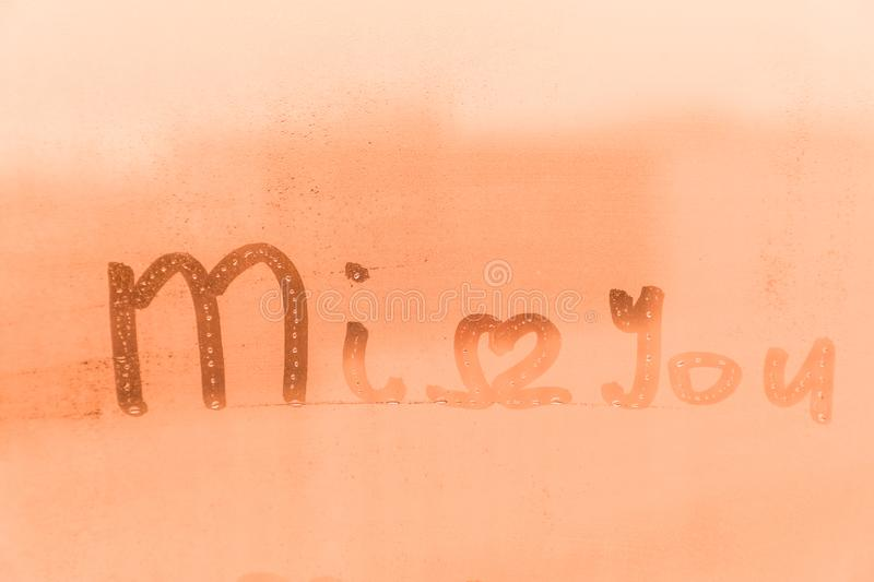 The romantic inscription miss you on the orange and pink evening or morning window glass royalty free stock photography