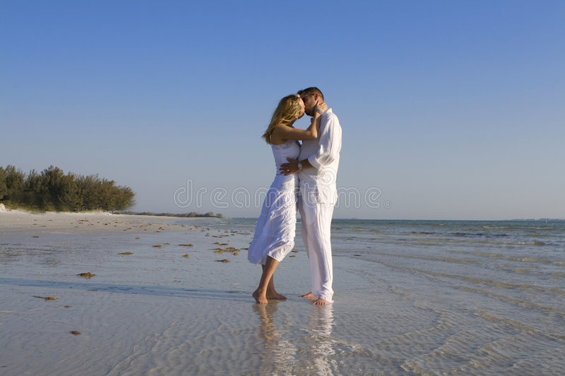 Romantic kiss. Man and a woman kissing on a beach. Both wearing white clothes royalty free stock photos