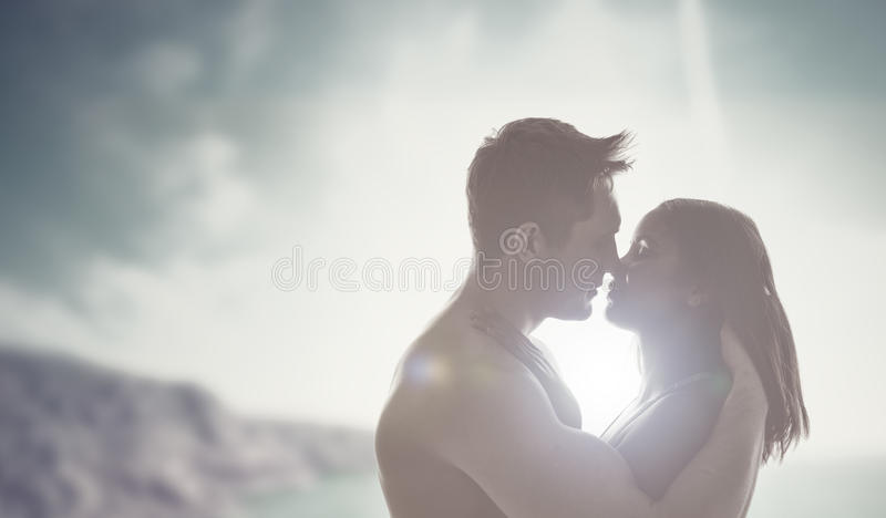 Romantic kiss backlit by the sun. Loving young couple enjoying a romantic kiss backlit by the sun with flare effect and a mountain background stock photo