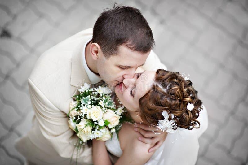 Romantic kiss bride and groom at wedding walk stock photo