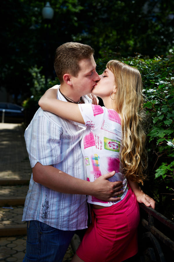 Romantic kiss of happy lovers. In beautiful park stock images