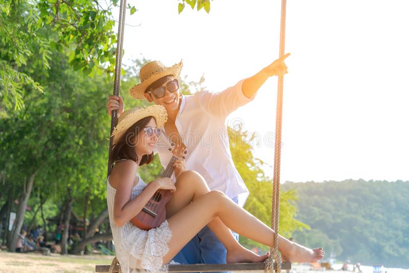 Romantic lifestyle asian couples lover playing an ukulele on the hammock. relax royalty free stock photo