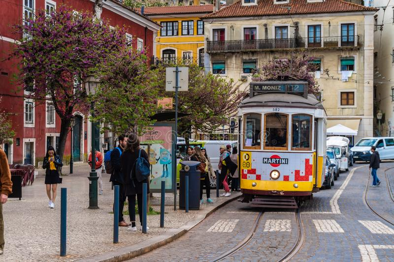 Romantic Lisbon street with the typical yellow tram, Portugal royalty free stock images