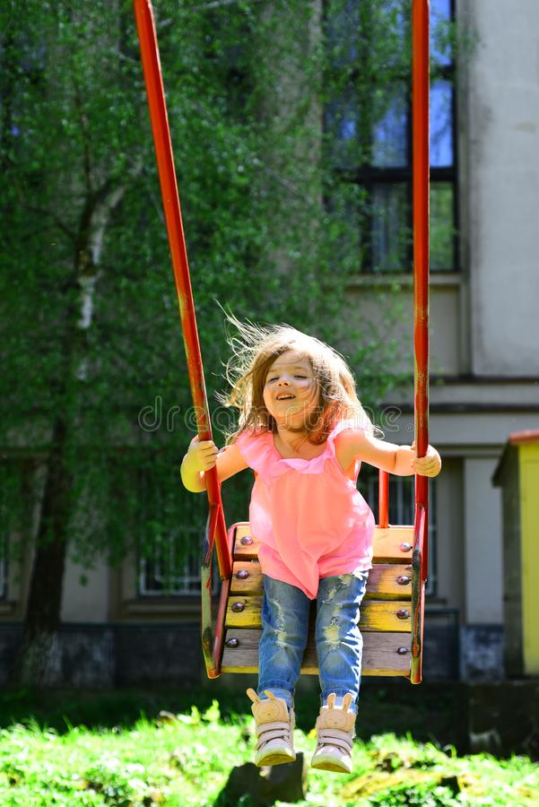 Romantic little girl on the swing, sweet dreams. childhood daydream. freedom. Playground in park. Small kid playing in stock image
