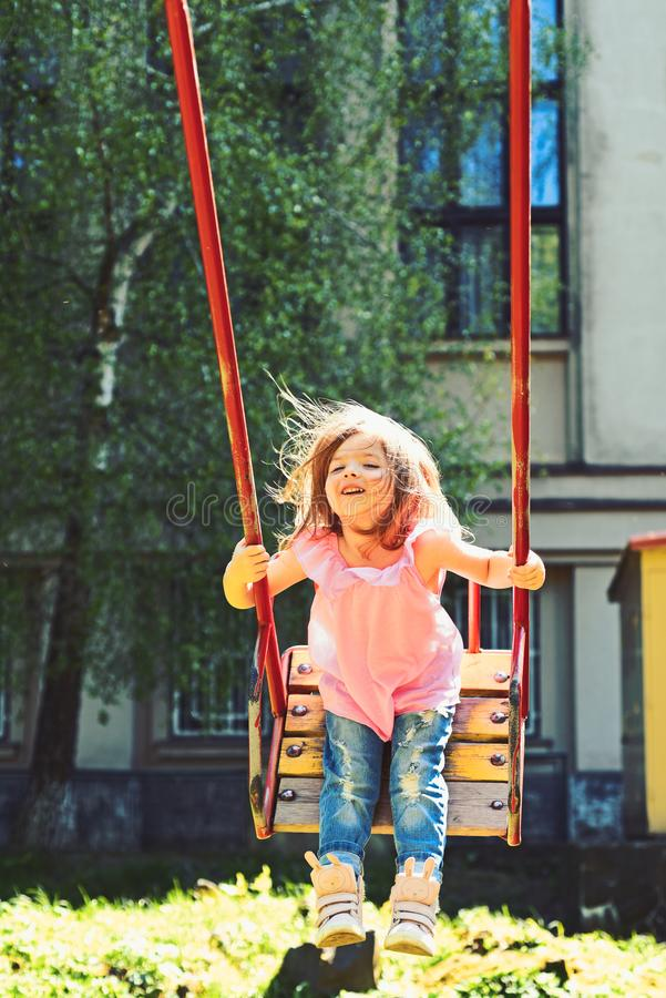Romantic little girl on the swing, sweet dreams. childhood daydream. freedom. Playground in park. Small kid playing in royalty free stock images