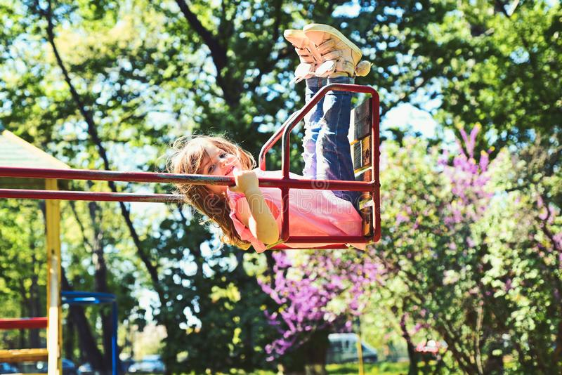 Romantic little girl on the swing, sweet dreams. Small kid playing in summer. childhood daydream .teen freedom stock photo