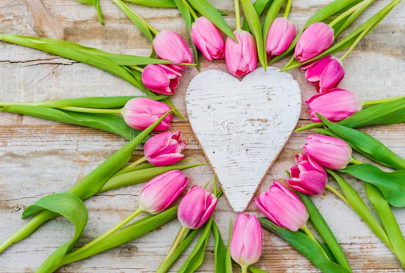 Romantic love background with rustic wooden heart shape and pink tulips flowers. Heart shape with pink tulip flowers and white love heart royalty free stock photos