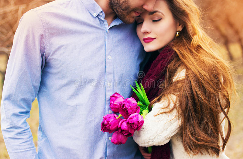 Romantic love story of beautiful young couple. Romantic love story. Close-up portrait of bearded men hugging his lovely girlfriend holding flowers. Beautiful stock photography