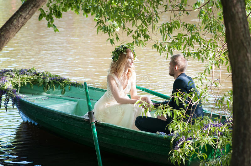 Romantic love story in boat. Woman with wreath and white dress. European tradition. Romantic love story in boat. Woman with wreath and white dress royalty free stock photo