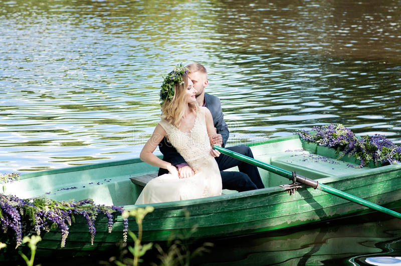 Romantic love story in boat. Woman with wreath and white dress. European tradition. Romantic love story in boat. Woman with wreath and white dress royalty free stock image