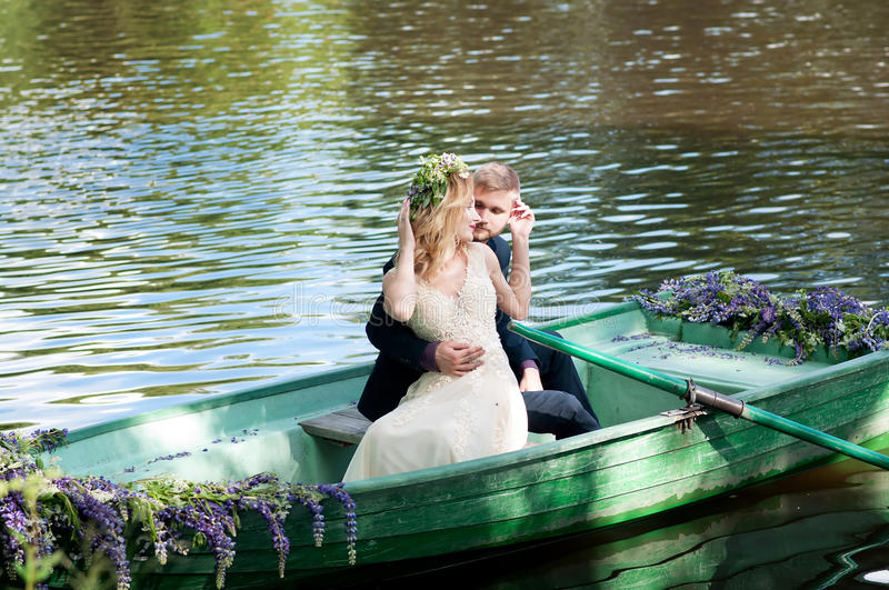 Romantic love story in boat. Woman with wreath and white dress. European tradition. Romantic love story in boat. Woman with wreath and white dress royalty free stock photos