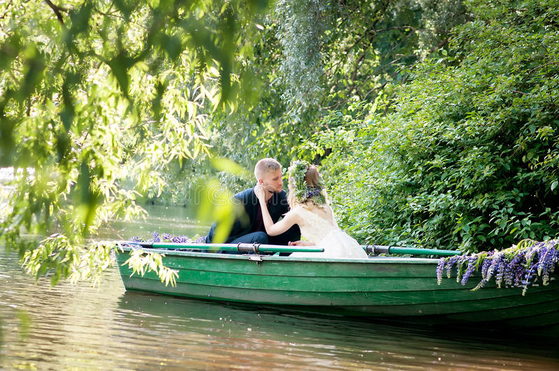 Romantic love story in boat. Woman with wreath and white dress. European tradition. Romantic love story in boat. Woman with wreath and white dress stock photography