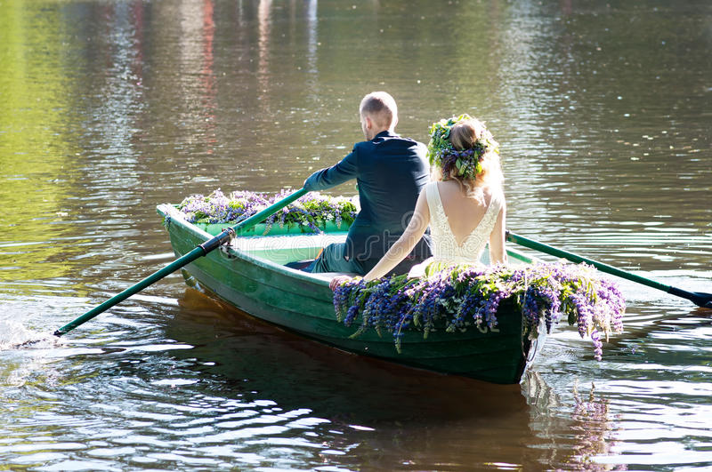 Romantic love story in boat. Woman with wreath and white dress. European tradition. Romantic love story in boat. Woman with wreath and white dress stock image