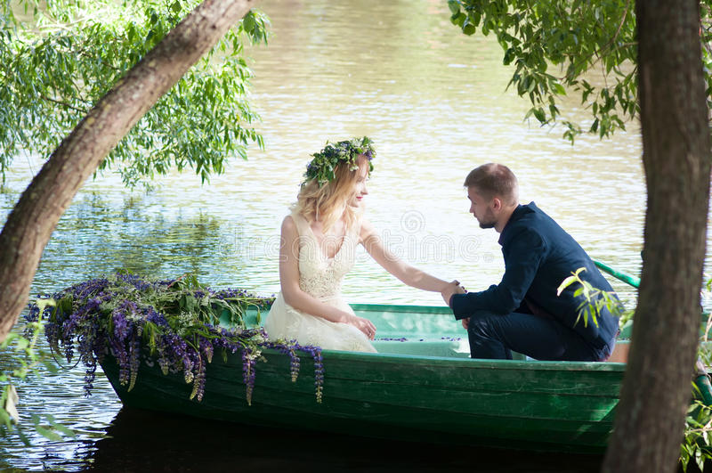 Romantic love story in boat. Woman with wreath and white dress. European tradition. Romantic love story in boat. Woman with wreath and white dress royalty free stock photography
