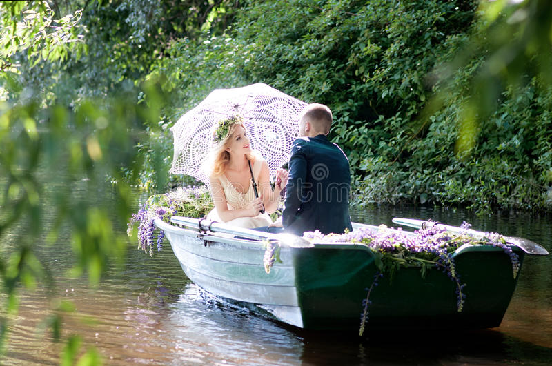 Romantic love story in boat. Woman with wreath and white dress. European tradition. Romantic love story in boat. Woman with wreath and white dress stock photos