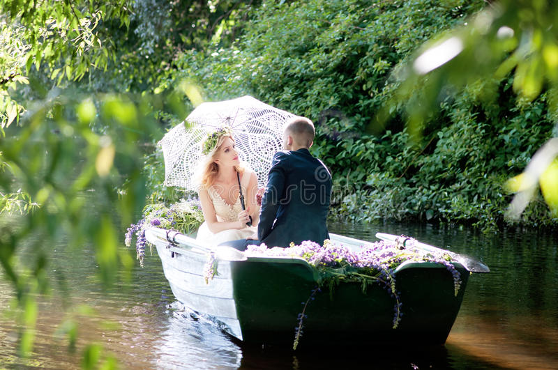 Romantic love story in boat. Woman with wreath and white dress. European tradition. Romantic love story in boat. Woman with wreath and white dress stock photo