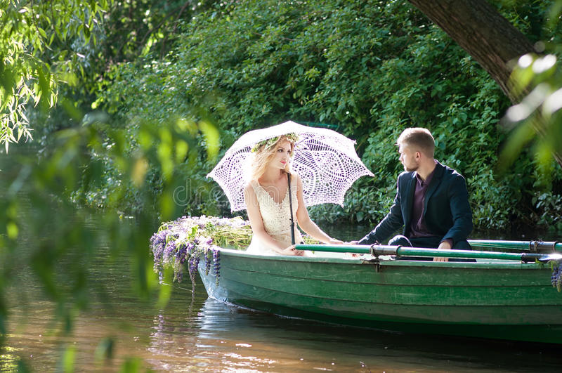 Romantic love story in boat. Woman with wreath and white dress. European tradition. Romantic love story in boat. Woman with wreath and white dress stock images