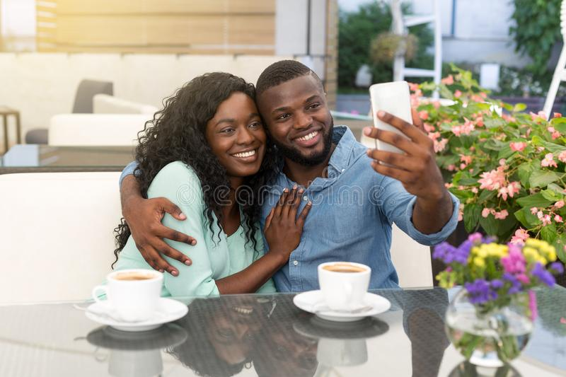 Romantic loving couple drinking coffee and taking picture, having a date in cafe royalty free stock photography