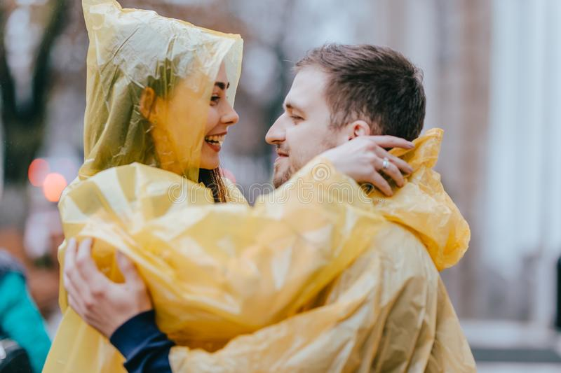 Romantic loving couple, guy and his girlfriend dressed in yellow raincoats are hugging on the street in the rain royalty free stock image