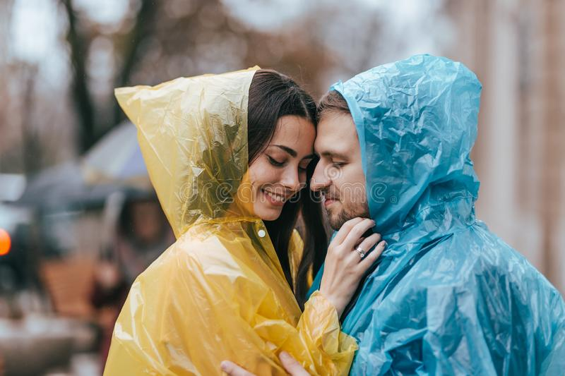 Romantic loving couple, guy and his girlfriend in the raincoats stand face to face on the street in the rain stock image