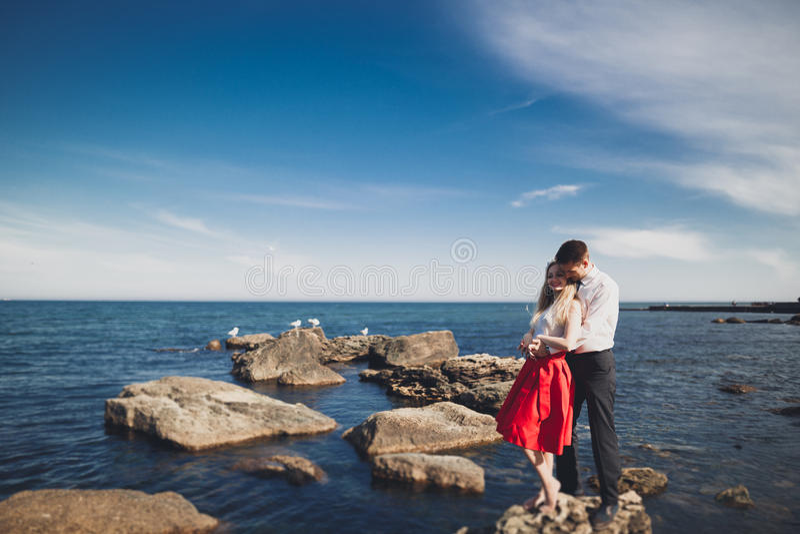 Romantic loving couple posing on stones near sea, blue sky royalty free stock image
