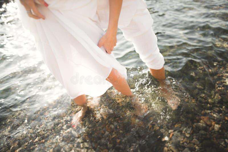 Romantic loving couple posing on stones near sea, blue sky.  stock photos