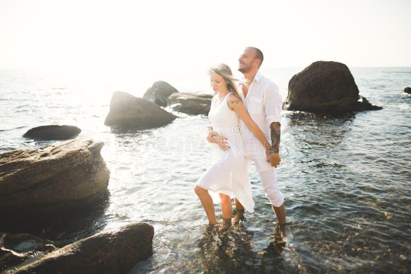 Romantic loving couple posing on stones near sea, blue sky.  royalty free stock photo
