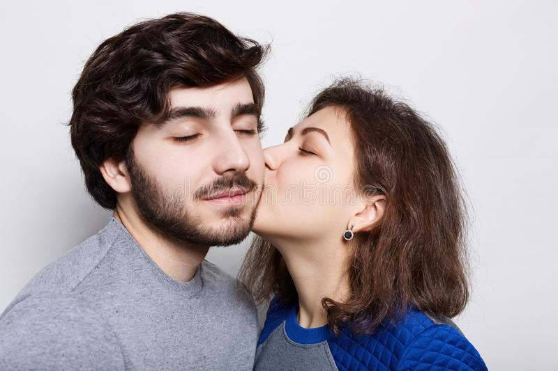Romantic loving couple. A pretty brunette kissing his bearded boyfriend in his chin. A happy couple closing their eyes from pleasu royalty free stock images