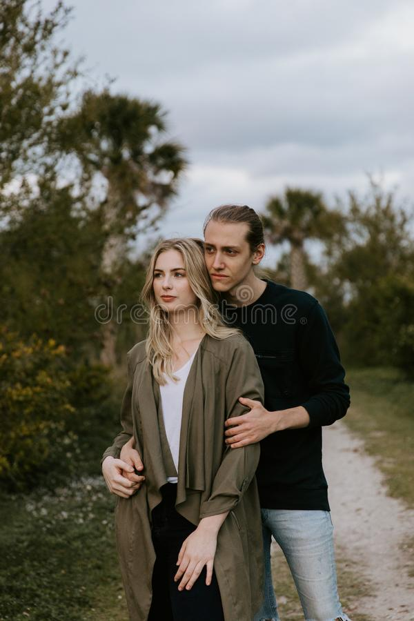 Romantic and Loving Young Adult Couple at the Park Looking At Nature and the Horizon for Portrait Pictures. Outside at the park during sunset stock photo